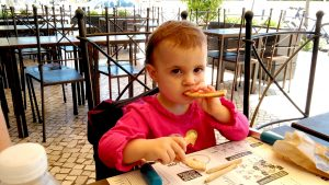 Sofia eating the pizza crusts at Dolce Vita